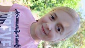 Piękna mała dziewczynka ma wideo gadkę używać smartphone Vertical ekran zdjęcie wideo