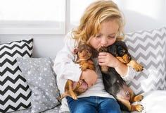 Piękna mała dziewczynka obejmuje dwa małego powabnego szczeniaka jamnik zdjęcie royalty free