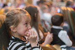 Piękna mała dziewczynka patrzeje zafascynowanego łasowanie popkorn ogląda film przy lokalną kino przekąski wiadra dżonką fotografia royalty free