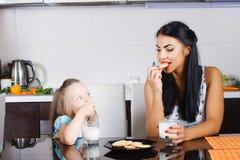 Piękna mała dziewczynka pije mleko i ciastka Zdjęcia Royalty Free