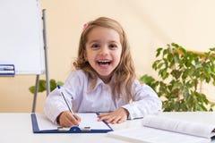 Piękna mała dziewczynka pisze obsiadaniu przy stołem fotografia royalty free