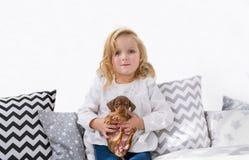Piękna mała dziewczynka pozuje z szczeniakiem w bedrooom obraz royalty free