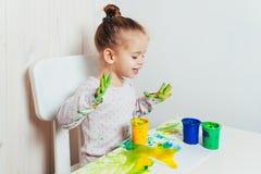 Piękna mała dziewczynka rysuje z palcowymi farbami na białym prześcieradle papier fotografia stock
