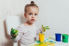 Piękna mała dziewczynka rysuje z palcowymi farbami na białym prześcieradle papier zdjęcie royalty free