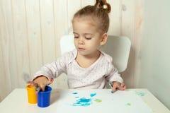 Piękna mała dziewczynka rysuje z palcowymi farbami na białym prześcieradle papier zdjęcia stock