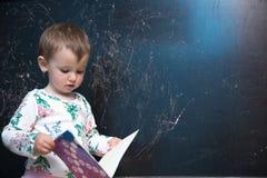 Piękna mała dziewczynka trzyma książkę Zdjęcia Royalty Free