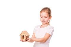 Piękna mała dziewczynka trzyma zabawkarskiego modela dom. Kupować domowego pojęcie. Zdjęcia Stock