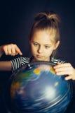 Piękna mała dziewczynka twirls kulę ziemską obraz stock
