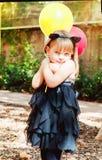 Piękna mała dziewczynka ubierał jako kot z balonami w rękach Słodki uśmiech, czuły spojrzenie obrazy royalty free