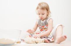 Piękna mała dziewczynka uczy się gotować posiłek w kuchni Zdjęcia Royalty Free
