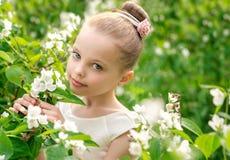 Piękna mała dziewczynka w białej sukni pozuje w trawie Zdjęcia Stock