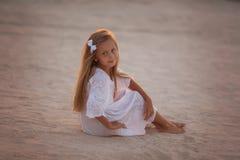 Piękna mała dziewczynka w biel sukni obsiadaniu na piasku w pustyni przy zmierzchem zdjęcie stock