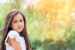 Piękna mała dziewczynka w parku z długie włosy i swee, i fotografia royalty free