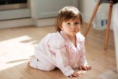 Piękna mała dziewczynka w piżamach na drewnianej podłoga Zdjęcia Stock