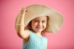 Piękna mała dziewczynka w plażowych kapeluszy stojakach nad menchiami odizolowywał tło fotografia royalty free