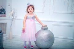 Piękna mała dziewczynka w smokingowej dekoruje choince odosobniony tylni widok biel Obraz Stock