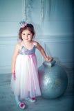 Piękna mała dziewczynka w smokingowej dekoruje choince odosobniony tylni widok biel Zdjęcia Royalty Free