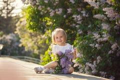 Piękna mała dziewczynka z bukietem bzy w wiośnie zdjęcie stock