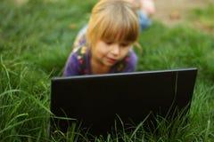 Piękna mała dziewczynka z laptopem Fotografia Stock