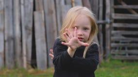 Piękna mała dziewczynka z niebieskimi oczami w czarnym pulowerze ciągnie jej ręki w kierunku zbiory wideo