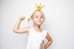Piękna mała dziewczynka z papierową koroną pozuje na białym tle w domu Obraz Royalty Free