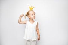 Piękna mała dziewczynka z papierową koroną pozuje na białym tle w domu Fotografia Royalty Free