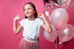 Piękna mała dziewczynka z piłkami na różowym tle, świętuje urodziny fotografia stock
