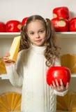 Piękna mała dziewczynka z serem w ręka przodzie półki Fotografia Stock