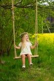 Piękna mała dziewczynka z wiankiem na jej głowie bawić się w flo Obraz Royalty Free