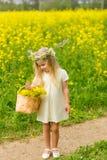 Piękna mała dziewczynka z wiankiem na jej głowie bawić się w flo Obraz Stock