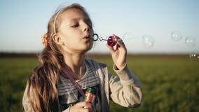 Piękna mała kobieta dmucha mydlanych bąble outdoors z długim blondynem _ Otwarta kamera z bliska zdjęcie wideo