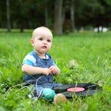 Piękna mała rozochocona chłopiec z rejestrem i hełmofony w lato parku Fotografia Stock