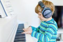 Piękna małe dziecko chłopiec z hełmofonami bawić się pianino w żywym pokoju lub muzycznej szkole Preschool dziecko ma zabawę z obrazy royalty free