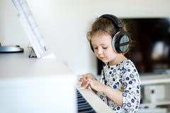 Piękna małe dziecko dziewczyna bawić się pianino w żywym pokoju lub muzycznej szkole Preschool dziecko ma zabawę z uczenie bawić  fotografia royalty free