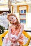 Piękna małej dziewczynki odzież w mody sukni obsiadaniu w kawiarni zdjęcia stock