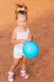 Piękna małej dziewczynki pozycja z błękitnym balonem w parku Obrazy Stock