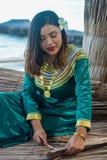Piękna maldivian kobieta w obywatelów smokingowych robi talerzach od suchych palmowych liści obrazy royalty free