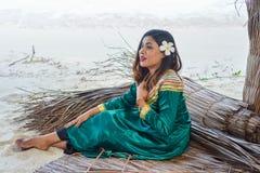 Piękna maldivian kobieta w obywatel sukni obsiadaniu na prześcieradłach robić od suchych liści fotografia royalty free