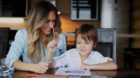 Piękna mama pomaga jej syna malować z barwionym ołówka wizerunkiem Pomagać rozwijać dziecka ` s wyobraźnię zbiory
