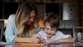 Piękna mama pomaga jej syna malować z barwionym ołówka wizerunkiem Pomagać rozwijać dziecka ` s wyobraźnię zbiory wideo