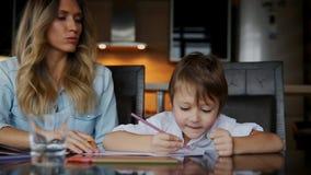Piękna mama pomaga jej syna malować z barwionym ołówka wizerunkiem Pomagać rozwijać dziecka ` s wyobraźnię zdjęcie wideo