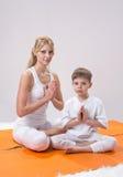 Piękna matka ćwiczy joga z jej synem zdjęcie royalty free