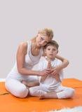 Piękna matka ćwiczy joga z jej synem obrazy royalty free