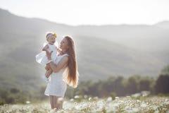 Piękna matka i jej córka bawić się w wiosna kwiatu polu Zdjęcia Royalty Free