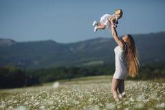 Piękna matka i jej córka bawić się w wiosna kwiatu polu Zdjęcie Stock