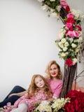 Piękna matka i miedzianowłosy córka stojak w uścisku przeciw tłu kwiaty w studiu Fotografia Royalty Free