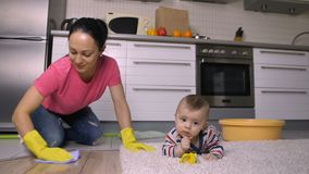 Piękna matka myje podłogowego pobliskiego dziecka na kolanach zbiory