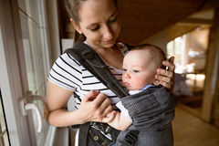 Piękna matka z jej ślicznym małym synem w dziecko przewoźniku obraz stock