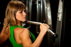 Piękna mięśniowa dysponowana kobieta ćwiczy budynków mięśnie w fitn Obrazy Stock