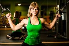 Piękna mięśniowa dysponowana kobieta ćwiczy budynków mięśnie w fitn Zdjęcia Stock
